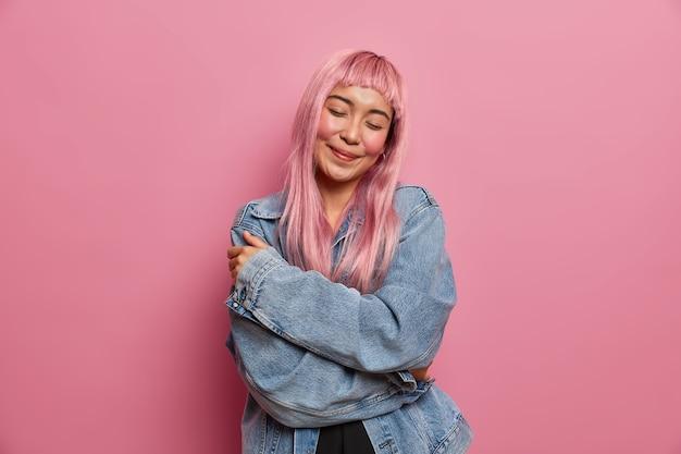 Stile di vita, concetto di emozioni umane. felice donna tenera con lunghi capelli rosei, abbraccia il proprio corpo e ama se stessa, sta con gli occhi chiusi, indossa una giacca di jeans