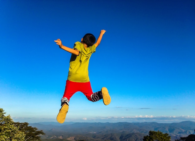 Lifestyle image of happy young boy jumping to the nature.