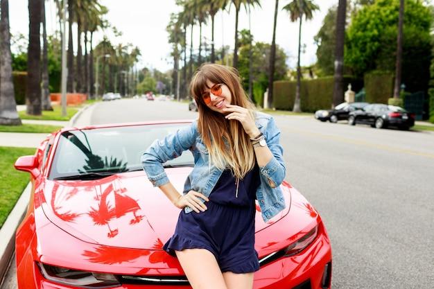 驚くべき赤いコンバーチブルスポーツカーのボンネットの上に座っている旅行女性のライフスタイルイメージ。ロサンゼルスの通り