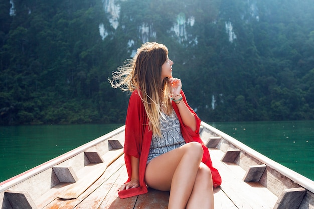 Lifestyle image of pretty travel woman sitting in wood long tail boat and looking on wild nature and mountains . explore and vacation concept. khao sok lake, thailand.