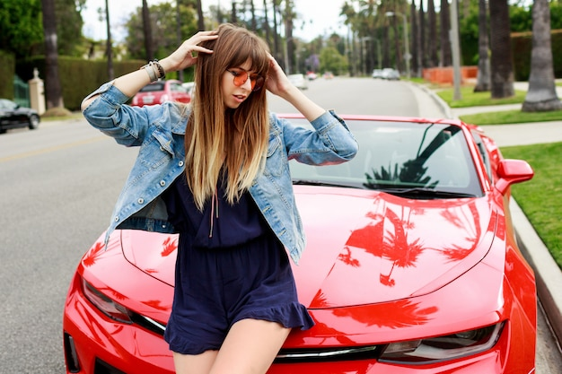 Lifestyle image of travel female sitting on the hood of amazing red convertible sport car. streets of los angeles.