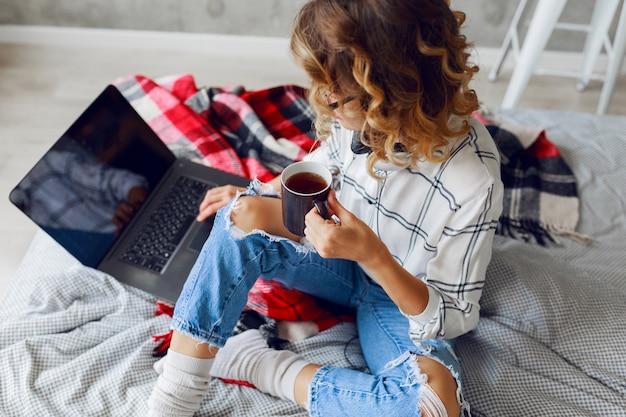 ライフスタイルのイメージ、コーヒーを飲みながらコンピューターを使う女性、暖かい靴下と流行のジーンズを着ています。ベッドに座る。朝早く。上面図。