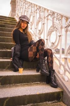 Образ жизни в городе, симпатичная кавказская брюнетка в коротком черном платье, берете и клетчатых чулках сидит, наслаждаясь летними каникулами.
