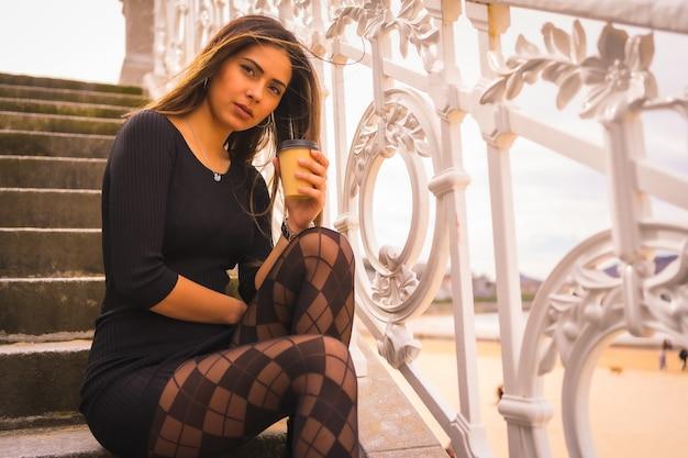 Образ жизни в городе, кавказская брюнетка в коротком черном платье и в клетчатых колготках сидит, наслаждаясь отдыхом летом