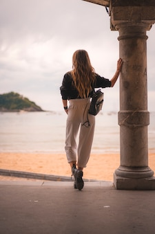 흰 바지에 금발 소녀와 해변 근처 가죽 자켓으로 도시의 라이프 스타일. 해변 기둥 옆의 사진