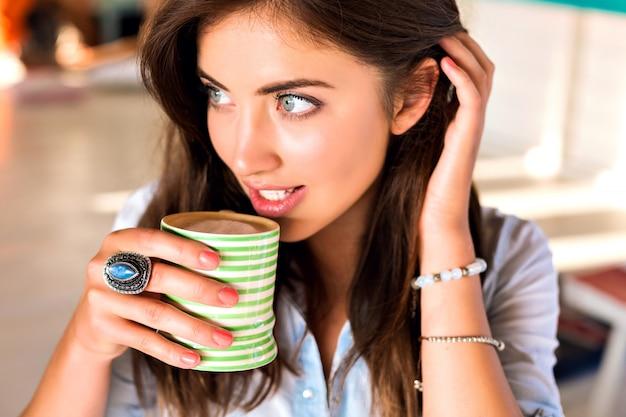 Образ жизни крытый портрет молодой брюнетки, позирующей в городском кафетерии, наслаждается ее вкусным горячим утренним кофе