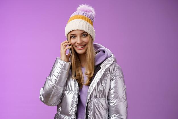 생활 양식. 즐거운 현대적인 세련 된 밀레 니얼 젊은 금발 소녀 이야기 친구 스마트 폰 전화 엄마 모자 실버 재킷을 입고 해외 겨울 리조트 휴가에서 귀 웃 고 근처 휴대 전화를 개최.