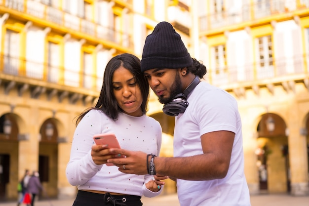 Lifestyle, latino black friends watching social media on the street