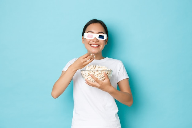 Концепция образа жизни, досуга и эмоций. улыбающаяся довольная азиатская девушка выглядит довольной, пока ест попкорн из миски, смотрит фильм на экране телевизора в 3d-очках, наслаждается потрясающими сериалами.