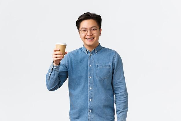 Образ жизни, досуг и люди концепция улыбающегося азиатского студента в очках и подтяжках, поднимающего чашку ...