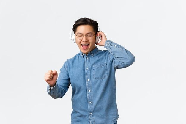 라이프 스타일, 레저 및 기술 개념. 안경에 행복 춤 아시아 남자, 음악 무선 헤드폰 듣기, 노래, 스트리밍 플랫폼에서 새 앨범과 함께 재미.