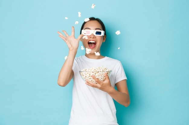 Lifestyle, leisure and emotions concept. impressed and excited asian girl enjoying watching movie, throwing popcorn at tv screen as wearing 3d glasses, standing light blue wall