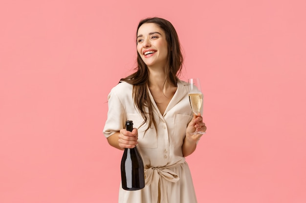 Lifestyle, modern women and beauty concept. alluring happy young brunette girl in pretty dress, laughing looking aside, open bottle champagne holding glass, drinking and partying