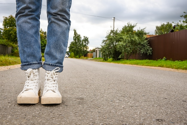 Lifestyle. modern young woman in a stylish blue jeans in fashionable white sneakers stands on road. stylish women's shoes. youth style. closeup of female legs in a trendy shoes.