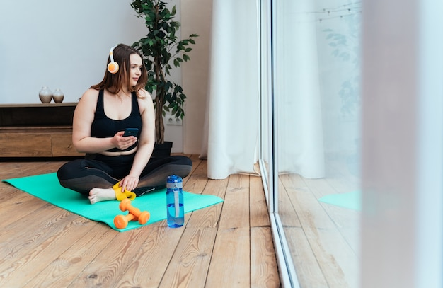 自宅で若い女性のライフスタイルの瞬間。居間でスポーツ運動をする女性