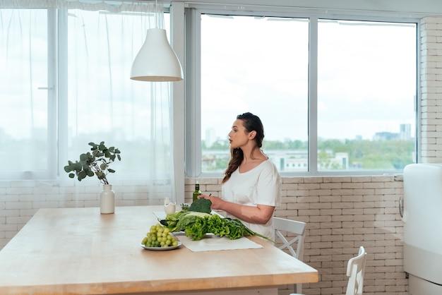 집에서 젊은 여성의 라이프 스타일 순간. 부엌에서 샐러드를 준비하는 여자