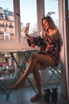 Образ жизни молодой блондинки, завтракающей рядом с продажей своего дома. одет в нижнее белье и пижаму, смотрит в соцсети