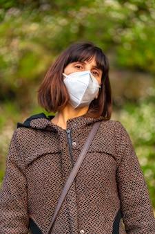 공원에서 백인 마스크와 젊은 갈색 머리의 라이프 스타일. 통제되지 않은 covid-19 전염병의 첫 걸음