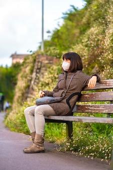 마스크는 나무 벤치에 앉아 젊은 갈색 머리의 라이프 스타일. 통제되지 않은 covid-19 전염병의 첫 걸음