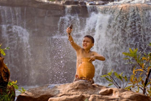 タイの田舎の子供たちのライフスタイル。少年は川で魚を捕まえるのを楽しんで。