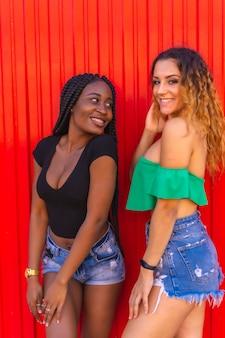 Образ жизни друзей кавказская блондинка и черная девушка с большой косой на красной стене
