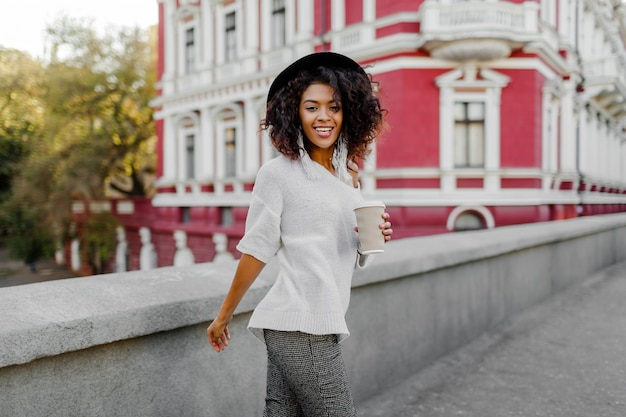 Lifestyle outdoor image of blissful black woman walking in spring  city with cup of cappuccino or hot tea. hipster outfit. oversize white sweater, black hat, stylish accessories.