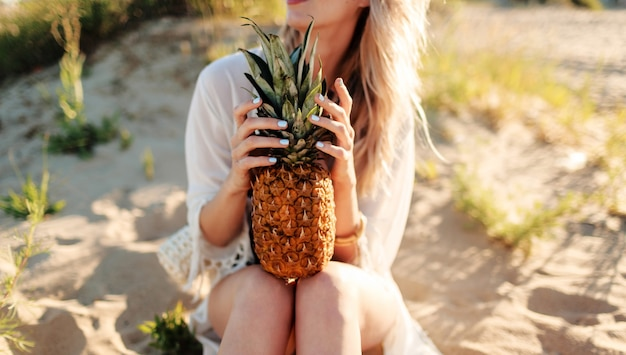 Lifestyle outdoor picture of laughing pretty woman with juicy pineapple relaxing on sunny beach . trendy summer outfit