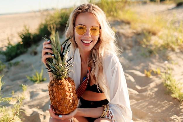 Изображение жизни на открытом воздухе смеясь над красивой женщиной с сочным ананасом, расслабляющимся на солнечном пляже. модный летний наряд