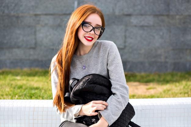 Образ жизни на открытом воздухе портрет красивой рыжей девушки в прозрачном стекле и кашемировом сером свитере, позирующей в парке в осенне-зимнем стиле. держит рюкзак.