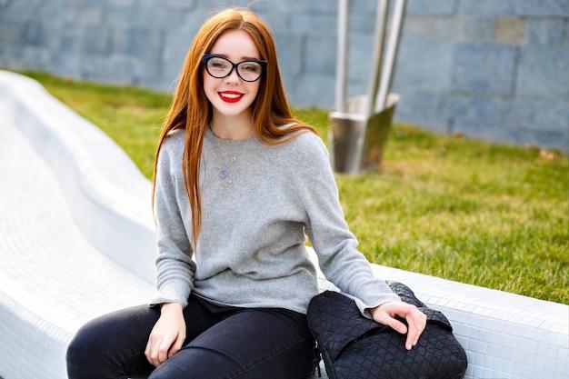 맑은 유리와 캐시미어 회색 스웨터를 입고 예쁜 생강 소녀의 라이프 스타일 야외 초상화, 공원, 가을 겨울 스타일에서 포즈.