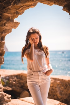 Lifestyle of a pensive young red-haired caucasian girl dressed in white by the sea, in a stone window