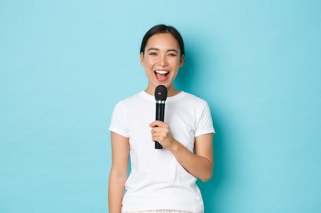 ライフスタイル、人々、レジャーのコンセプト。幸せなのんきなアジアの女の子は、歌を演奏し、カラオケマイクを持って笑顔を楽しんで、好きな歌を歌い、青い背景に立っています。