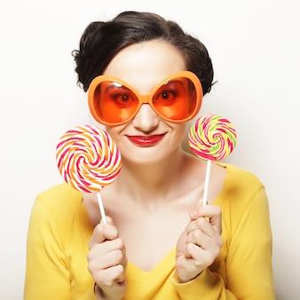 ライフスタイル、人々、パーティーのコンセプト:大きなロリポップを保持している大きなオレンジ色の眼鏡をかけている面白い女性。誕生日会。