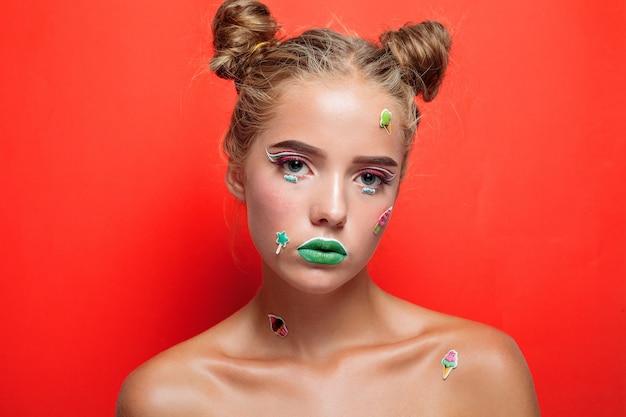 ライフスタイル、人、美しさ、創造的なコンセプト-美しい若い女性は、広く笑顔のキャンディーを手に持っています。彼女の手に明るい化粧とキャンディー、ピンクの背景で隔離のスタイリッシュな女の子