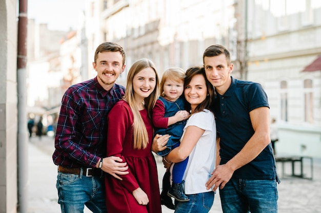 Lifestyle and people concept: group of happy young friends standing together and having fun on city street. looking at camera. close up image. outdoors.