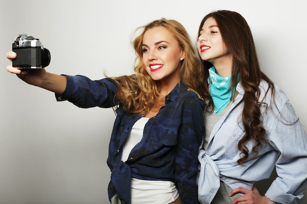 Lifestyle and people concept: happy girls friends taking some pictures, over grey background