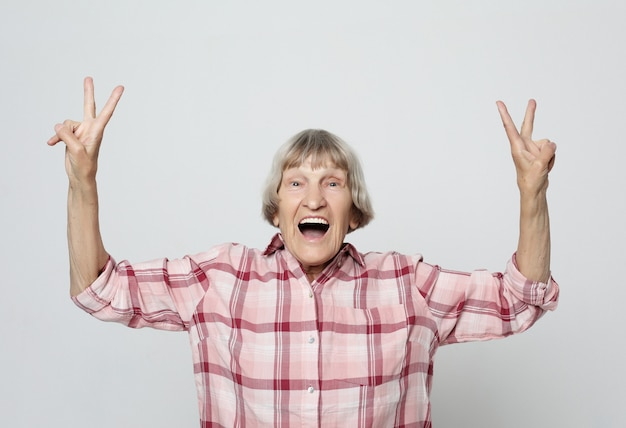Lifestyle and people concept: portrait of a cheerful grandmother gesturing victory
