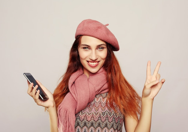 Lifestyle and people concept of portrait of a satisfied casual girl holding mobile phone
