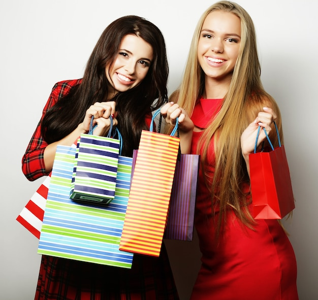 Lifestyle and people concept: two young women wearing red dress with shopping bags. big sale.