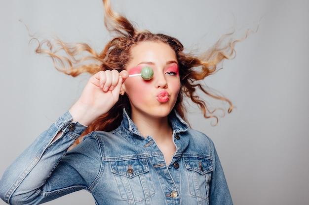 라이프 스타일, 사람, 붉은 입술으로 갈색 머리 여자 초상화의 창조적 인 개념 클로즈업 초상화. 아름 다운 젊은 여자는 광범위 하 게 웃 고 손 사탕에 보유하고있다. 세련된 소녀 밝은 화장과 사탕