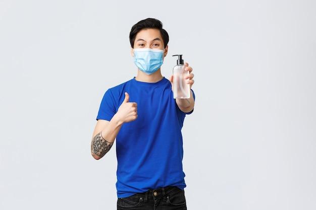 생활 방식, 사람들의 다른 감정, covid-19 전염병 개념. 의료용 마스크를 쓴 친절하고 잘 생긴 아시아 남자는 코로나바이러스 동안 손 소독제를 사용하는 중요성을 설명하고 엄지손가락을 위로 보여줍니다