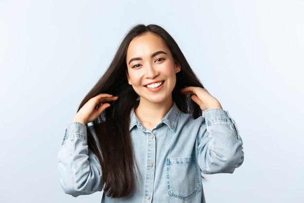 Образ жизни, эмоции людей и понятие красоты. привлекательная мечтательная азиатская девушка улыбается и трогает длинные прямые темные волосы, пробует новые продукты для волос, посещает парикмахерскую или салон красоты