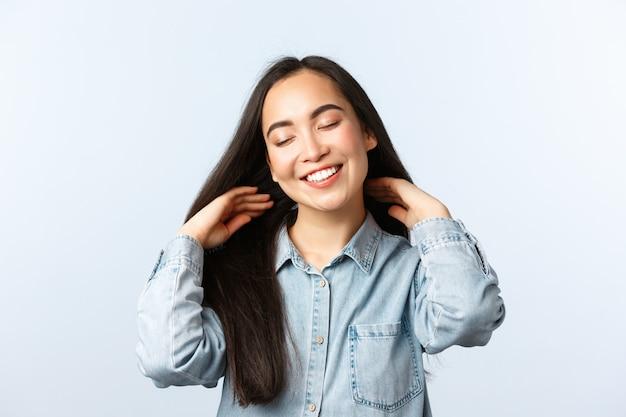 Образ жизни, эмоции людей и понятие красоты. беззаботная привлекательная азиатская девушка заботится о длинных темных волосах, демонстрирует красивую прическу, делает новую стрижку, закрывает глаза и удовлетворенно улыбается