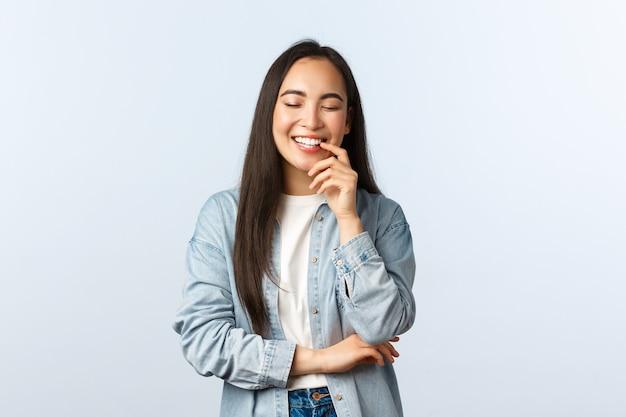 Образ жизни, эмоции людей и понятие красоты. беззаботная восторженная азиатская женщина с длинными темными волосами, закрытыми глазами и смеющейся над забавной ситуацией, выражает позитив и радость.