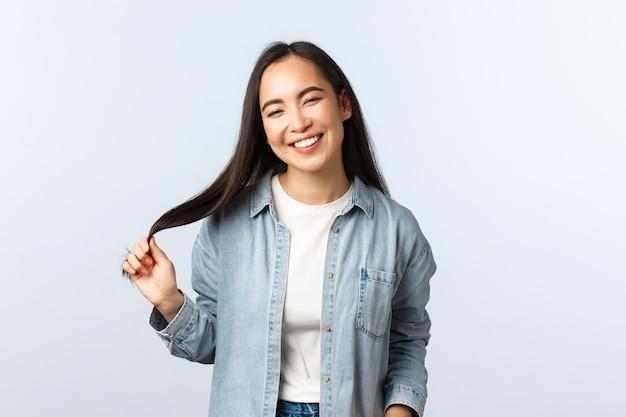 Образ жизни, эмоции людей и понятие красоты. беззаботная счастливая улыбающаяся исходящая женщина. азиатская девушка смеется и трогательно волосы, наслаждаясь визитом в салон красоты, белый фон.