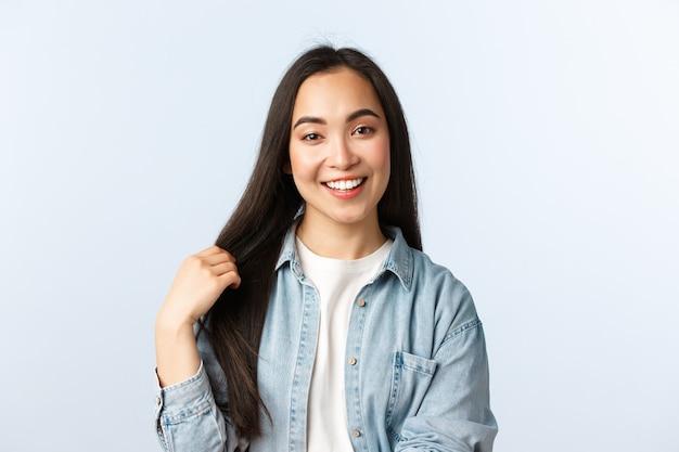 Образ жизни, эмоции людей и понятие красоты. беззаботная молодая азиатская женщина разговаривает и улыбается, трогательно волосы, рекомендует средства по уходу за волосами или салон красоты, белый фон.