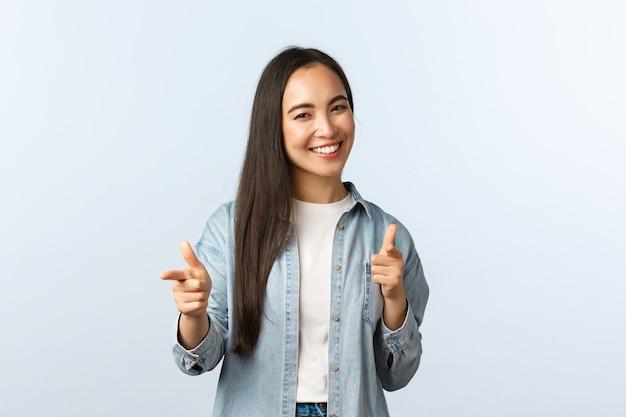 Образ жизни, эмоции людей и понятие красоты. дерзкая дружелюбная азиатская женщина поздравляет друга, хвалит хорошую работу или говорит, что хорошо покрыта, как показывает пальцами камеру и улыбается
