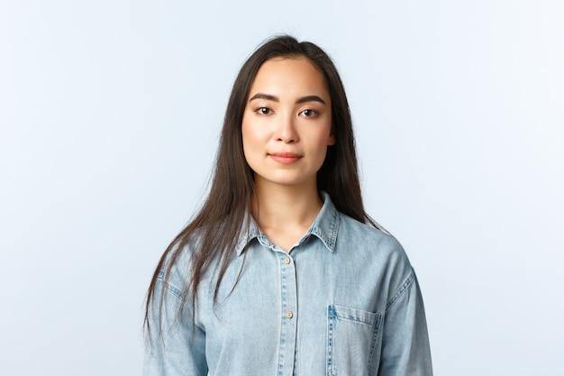 Образ жизни, эмоции людей и понятие красоты. веселая азиатская девушка в повседневной одежде смотрит в камеру с довольной улыбкой, сотрудник начинает новую работу в первый же день, продавец слушает клиента