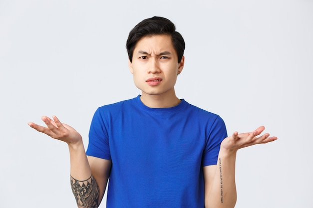 Образ жизни, эмоции людей и понятие красоты. растерянный и нерешительный молодой азиатский мужчина не может понять, что произошло, пожимая плечами, разводя руками и недоумевая гримасу, носит синюю футболку