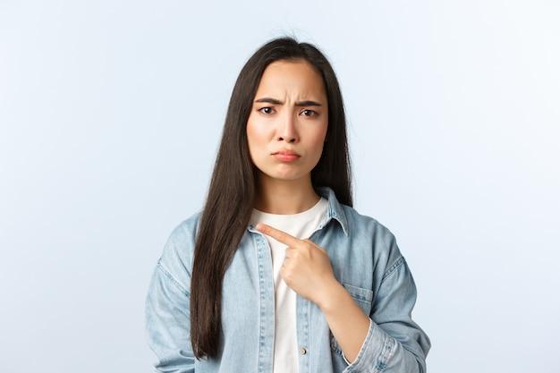 라이프 스타일, 사람들의 감정과 아름다움 개념. 실망한 우울한 여성 고객은 제품에 동의하지 않거나 제품을 싫어하고, 찡그린 얼굴을 하고 불만을 토로하며, 나쁜 것을 왼쪽으로 가리키는 손가락을 가리킵니다.